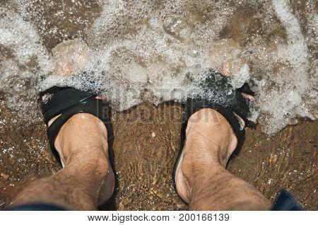 men feet with flip flops above the sea