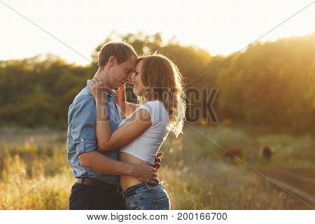 Couple in love. Tenderness and embrace. The guy and the girl look into each other's eyes. Sunset.