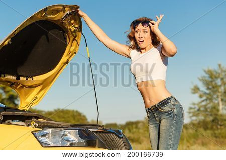 A young attractive girl opened the hood of the car and was trying to figure out the breakdown. Trouble on the road.