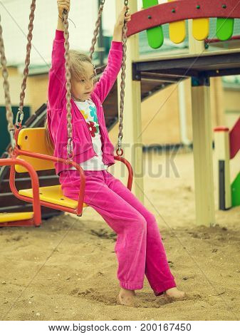 The girl in the red suit is sad on the swings on the beach. Dream about good weather and summer.