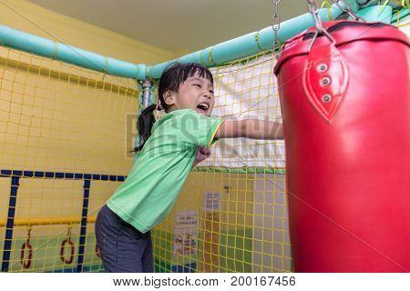 Asian Chinese Little Girl Playing With Punching Bag