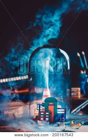 Handcrafted paper industrial plant with smoke under glass dome. Still life with blue collar workplace. Dark background with copy space.