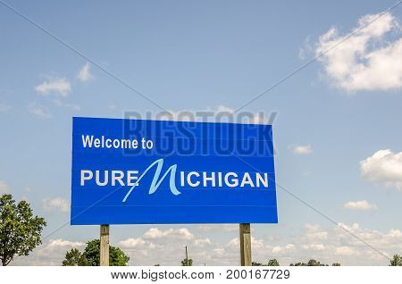 Blue and white sign welcomes travelers to Pure Michigan