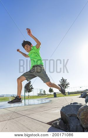 A young boy leaps off a rock in a park on a bright summer day.