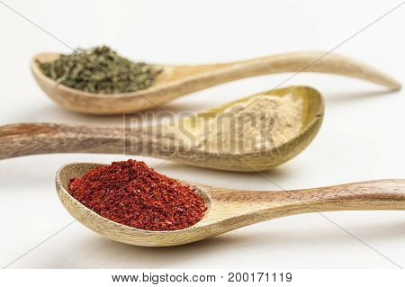 Wooden spoons of cooking herbs filled with red pepper powder garlic powder and basil leaves.