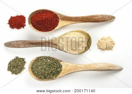 Cooking spices in spoons and piles filled with red pepper powder garlic powder and basil leaves.