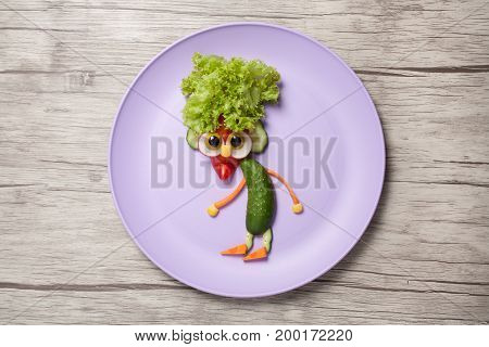 Gnome made of fresh vegetables on plate and desk