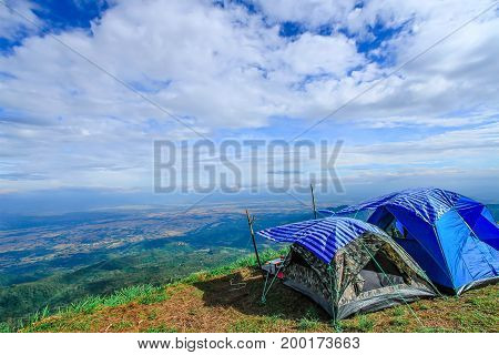 Man in orange jacket looking at view of mountain landscape with waves of fog and cloudy sky. Blue yellow camping tents on mountain peaks at Phu Tub Berg Phetchabun province Thailand