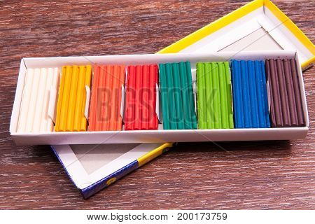 Photo children's colored plasticine isolated on vintage background. Materials for creativity.