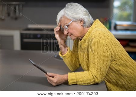 Tensed senior woman using digital tablet in the kitchen