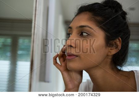 Woman touching face by mirror in bathroom at home