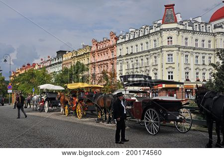 Carlsbad, Czech Republic - September 2014: Horse carriages waiting in line for passengers, in Carlsbad in September 2014, with some people passing