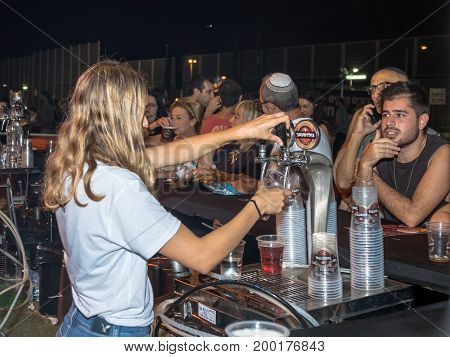 Haifa Israel August 16 2017 : The seller pours cold fresh beer to the visitor in a plastic glass at the traditional annual beer festival in the city of Haifa in Israel