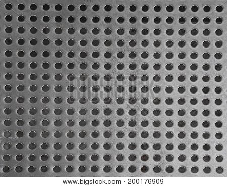 iron stainless steel grating with small regular circle shaped holes black and white geometric background