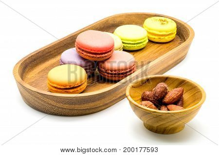Sweet macarons in wooden tray and almonds in wooden bowl on white background
