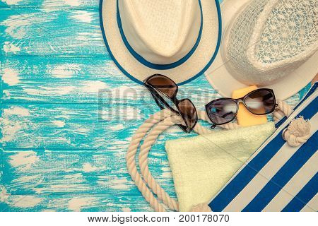 Beach accessories lie on a blue wooden background