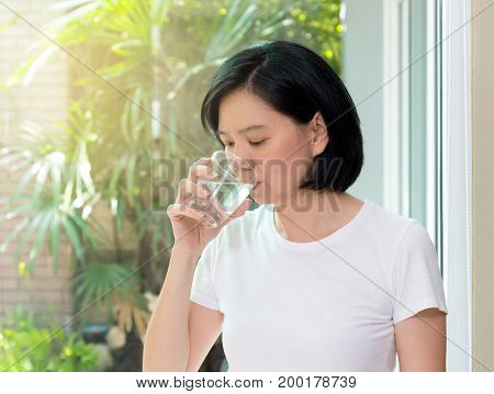 Beautiful Asian woman with clean skin natural make-up short black hair drinking water at home. Middle aged woman holding transparent glass in her hand. Image for skin and healthy concept copy space
