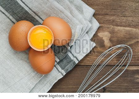 Top view on fresh eggs and whisk for whipping. Cooking concept.
