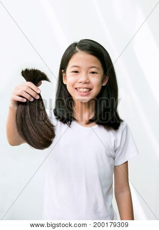 Teenage girl donating her healthy hair to cancer patients. Asian kid holding and showing her ponytail after haircut generously donating her long hair for making wigs for cancer patient who lost hair