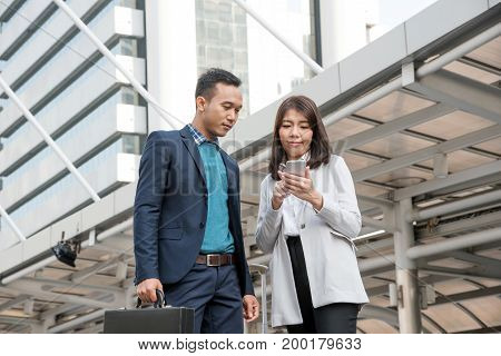 Happy Asian business people standing and discussing business project. Young Co-workers businesswoman with smartphone speaking with businessman on breaking time relaxing outdoor with urban background.