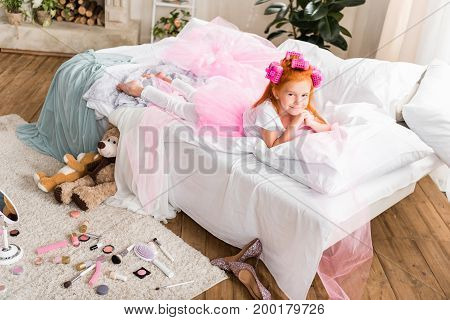 Little Girl With Curlers Resting On Bed