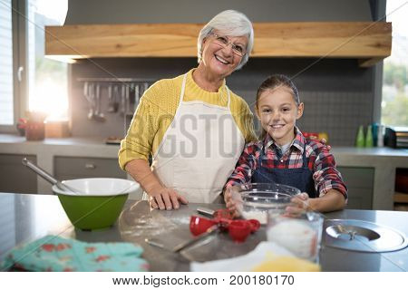 Close-up of smiling grandmother and granddaughter holding a bowl of flour in the kitchen