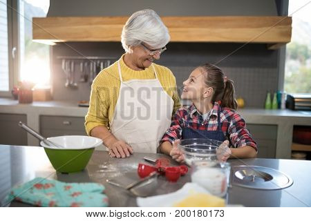 Smiling grandmother and granddaughter looking at each other while holding a bowl of flour in the kitchen
