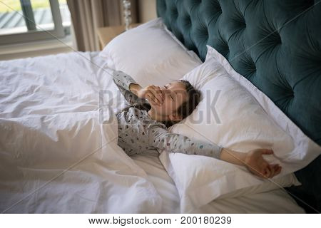 Girl yawning while stretching her arms in bed at home