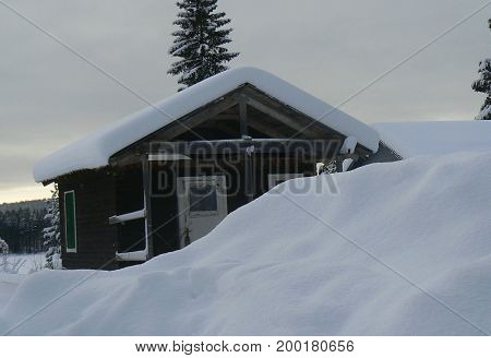 old abandoned wooden cabin in the snow