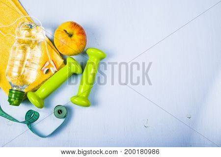 Dumbbells an apple a towel and a bottle of water on a blue wooden table. Concept of fitness and a healthy lifestyle.