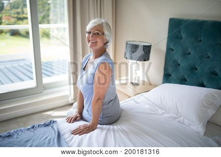 Portrait of smiling senior woman sitting on bed in bedroom
