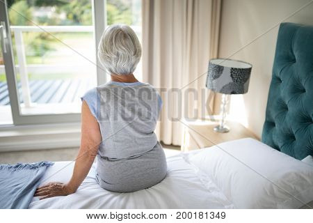 Rear view of senior woman sitting on bed in bedroom