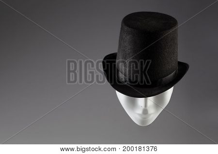 White mask hiding eyes under black top hat on grey background with copy space. Incognito concept