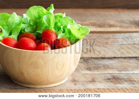 Fresh tomato and lettuce in wood bowl put on wood table. Side view of tomato and green oak lettuce with copy space for background. Fresh green oak lettuce and tomato prepare for cooking.