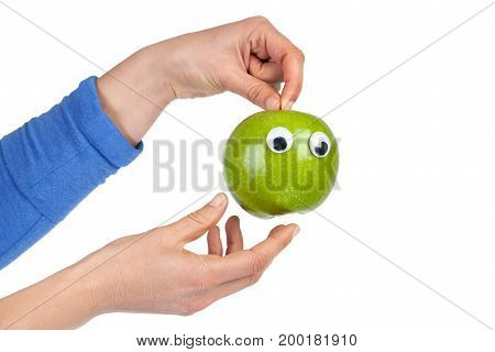 Female hands holding green apple with googly eyes isolated on white background with copy space. Healthy food and lifestyle concept