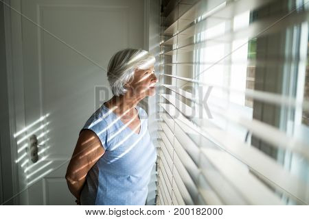 Senior woman looking through window in bedroom at home