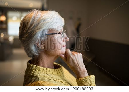 Thoughtful senior woman standing at home