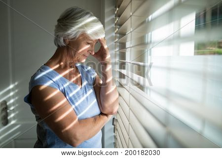 Tense senior woman standing near window in bedroom at home