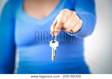 Woman holding home keys in front of her body. Shallow depth of field
