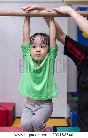 Asian Chinese little girl hanging on horizontal bar in gym class