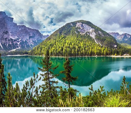 Magnificent lake in South Tyrol, Italy. The concept of walking and eco-tourism. Green expanse of water reflects the surrounding mountains and forest