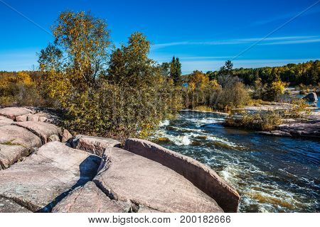 Old Pinava Dam. Warm clear autumn day. Foam water rapids on the smooth stones of the Winnipeg River. The concept of ecological and adventure tourism