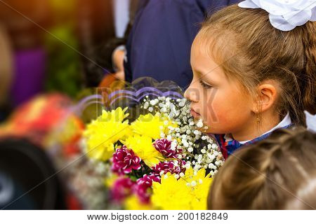 Little first-grader girl-student goes to school on knowledge day - September First. Student of elementary school in uniform with bows and flowers. Russia