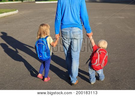 father taking kids to school or daycare, back to school