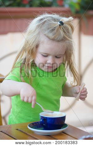 Healthy breakfast for child. Little kid boy making tea. Boy child mixing sugar in blue cup. Child boy with blond long hair mixing sugar with teaspoon. Childhood and baby care concept.