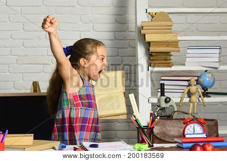 Schoolgirl With Cheerful Face Holds Book And Yells