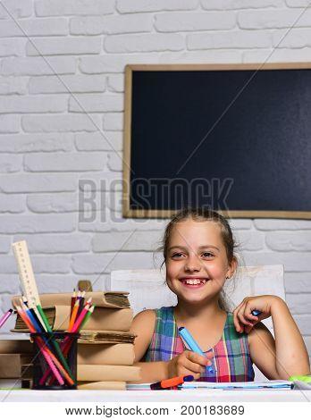 Schoolgirl With Happy Smile Draws In Her Art Book