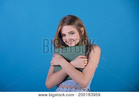 Youth and skincare. Beauty and fashion. Fashion model on blue background. Woman with long hair and makeup. Girl in dress with green book.