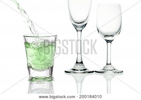 green cocktail with splashes on white background