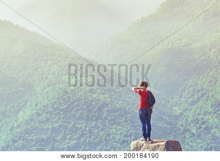 Woman with backpack standing on the rock at sunrise and enjoying breathtaking view in the mountains